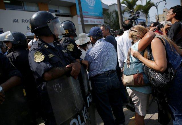 Los partidarios del ex presidente de Perú, Alan García, reaccionan al lado de los oficiales de policía, luego del anuncio de que García murió en un hospital luego de dispararse a sí mismo, en Lima, Perú, el 17 de abril de 2019. REUTERS / Janine Costa
